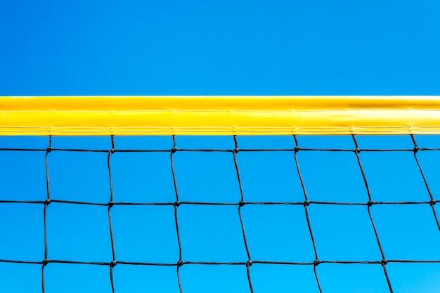 Żółte kolorowe letnie gry piłka tło - siatkówka plażowa lub siatka do tenisa na tle błękitnego nieba na imprezy sportowe. miejsce. kopiuj przestrzeń
