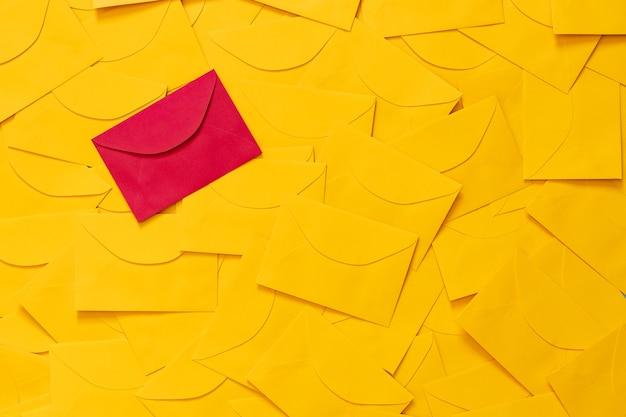 Żółte koperty rozrzucone na stole, z miejscem na tekst na białym papierze i podświetloną czerwoną kopertą. widok z góry.