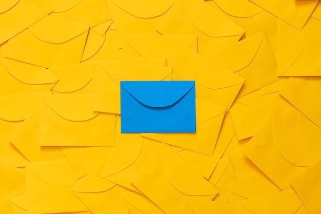 Żółte koperty rozrzucone na stole, z miejscem na tekst na białym papierze i podświetloną niebieską kopertą, widok z góry.