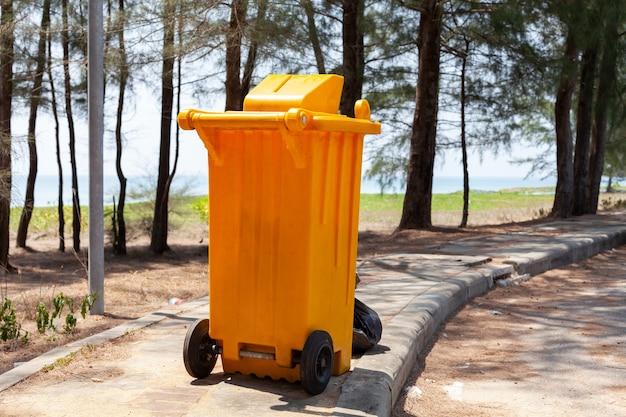 Żółte kosze na śmieci w parku blisko morza.