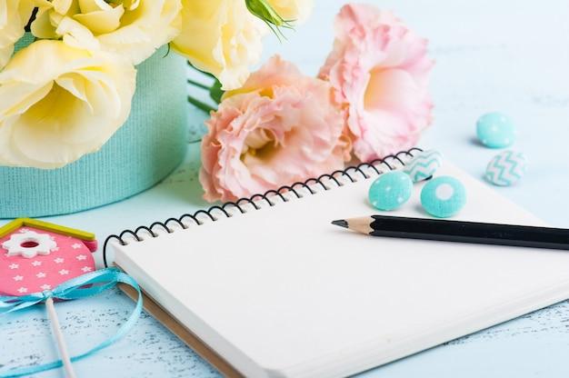 Żółte kwiaty eustoma i otwarty notatnik
