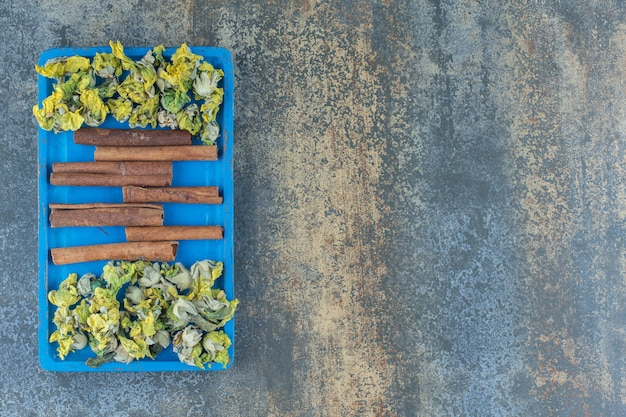 Żółte kwiaty i laski cynamonu na niebieskim talerzu.