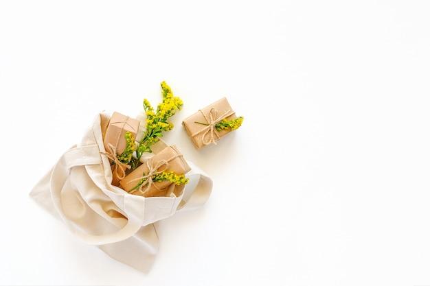 Żółte kwiaty i prezenty rzemieślnicze wylatują tekstylną torbę na zakupy na białym tle