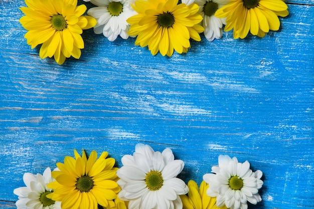 Żółte kwiaty na pomalowanym drewnianym tle tekstu