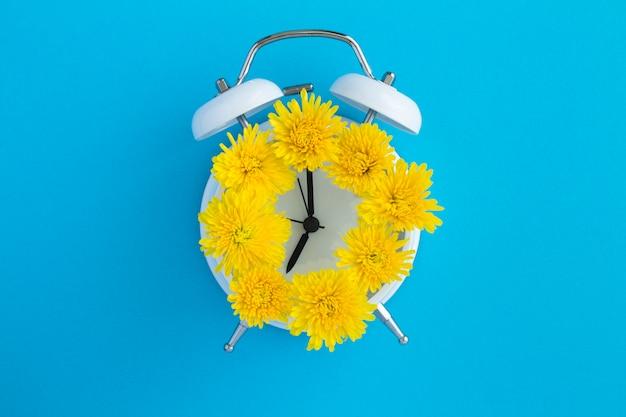 Żółte kwiaty na tarczy białego budzika pośrodku niebieskiej powierzchni