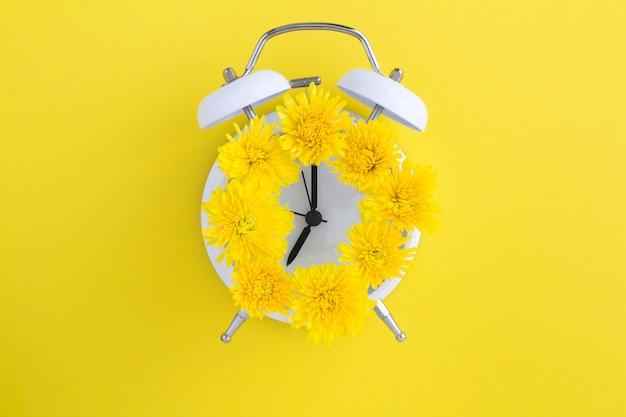 Żółte kwiaty na tarczy białego budzika pośrodku żółtej powierzchni