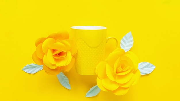Żółte kwiaty sztuczne i żółta filiżanka na żółtym tle