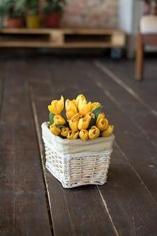 Żółte kwiaty w koszu na ciemnej podłodze