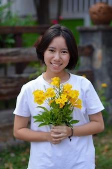 Żółte kwiaty w rękach kobiety
