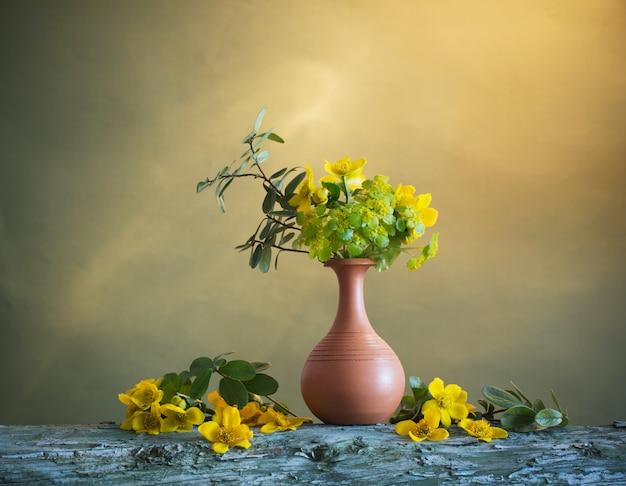 Żółte kwiaty w wazonie na drewnianym stole