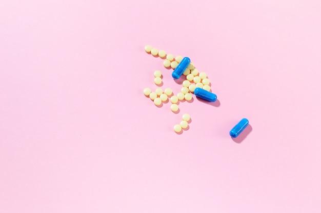 Żółte leki z nagimi kapsułkami na różowym tle z twardymi cieniami.