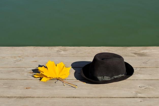 Żółte liście klonu i czarny kapelusz na molo