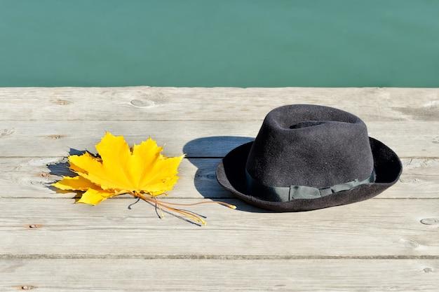 Żółte liście klonu i czarny kapelusz na przystani.