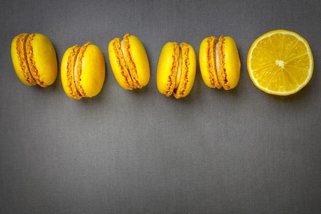 Żółte makaroniki cytrusowe i plasterek świeżej pokrojonej cytryny na szarym tle