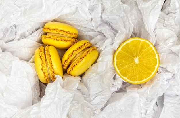 Żółte makaroniki cytrusowe i plasterek świeżo pokrojonej cytryny