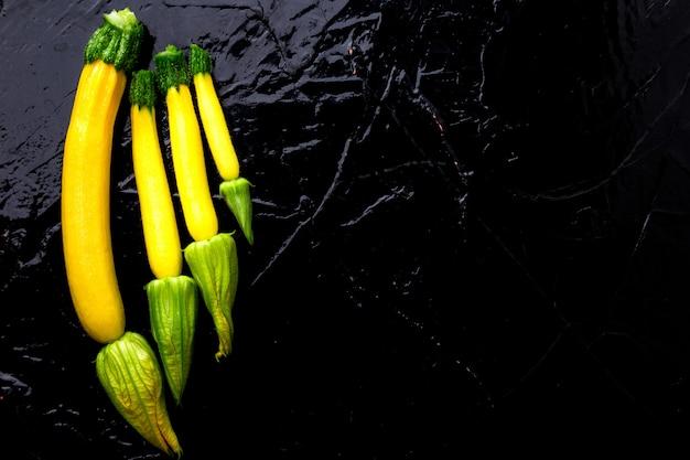 Żółte małe cukinie z kwiatkiem na czarnym stole