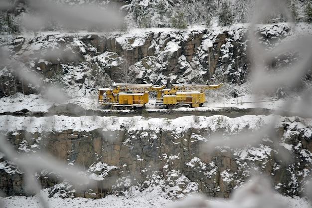 Żółte maszyny górnicze na zboczach kamieniołom granitu