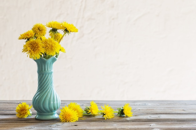 Żółte mlecze w niebieskim wazonie na białym tle