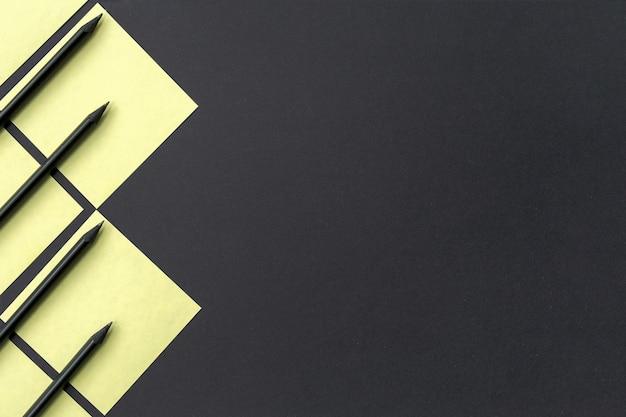 Żółte naklejki z czarnymi ołówkami wyłożone geometrycznym wzorem na czarnym tle