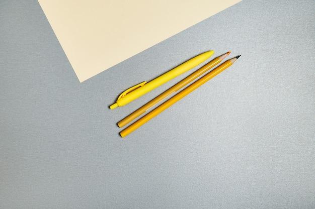 Żółte narzędzia do pisania wyczerpujące obok kartki żółtego papieru na szarej powierzchni.