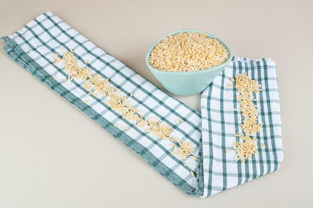Żółte nasiona ryżu w ceramicznym kubku na betonie.