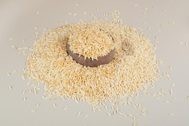 Żółte nasiona ryżu w drewnianym kubku na betonie.