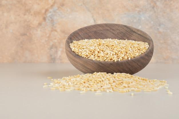 Żółte nasiona ryżu w drewnianym rustykalnym kubku na betonie.