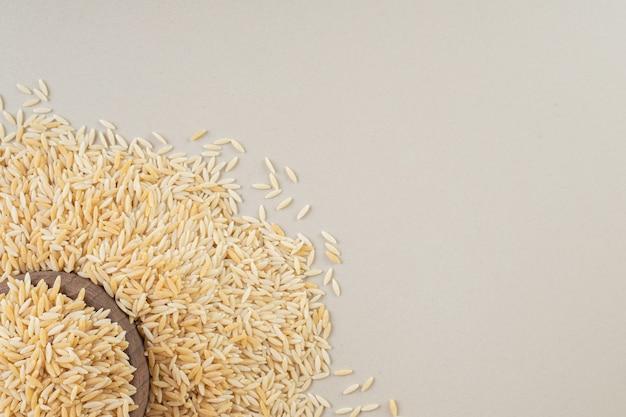 Żółte nasiona ryżu w filiżance na betonie.