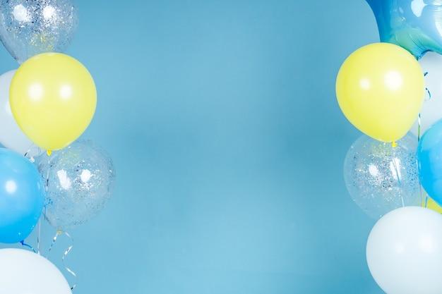 Żółte, niebieskie i białe balony na niebieskim tle ściany kopii przestrzeni. kolorowy balon w pokoju przygotowanym na przyjęcie urodzinowe. lato balony z helem.