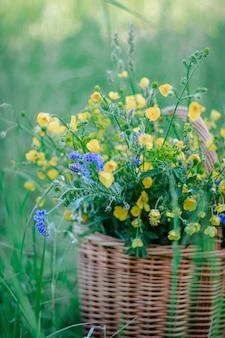 Żółte, niebieskie polne kwiaty w drewnianym wiklinowym koszu. kosz świeżych dzikich kwiatów w polu. miejsce na kopię. selektywne skupienie