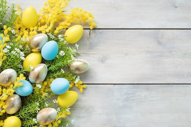 Żółte, niebieskie, złote jajka i gałęzie mimozy na białych drewnianych deskach