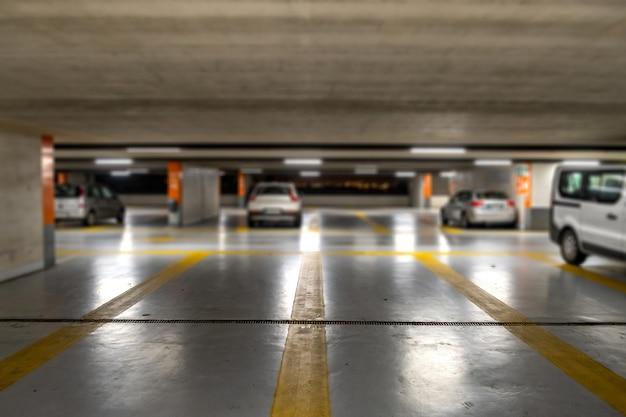 Żółte oznaczenia z niewyraźnymi nowoczesnymi samochodami zaparkowanymi na zamkniętym podziemnym parkingu.