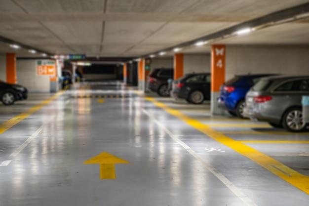 Żółte oznaczenia z zamazanymi nowoczesnymi samochodami zaparkowanymi na zamkniętym parkingu podziemnym.