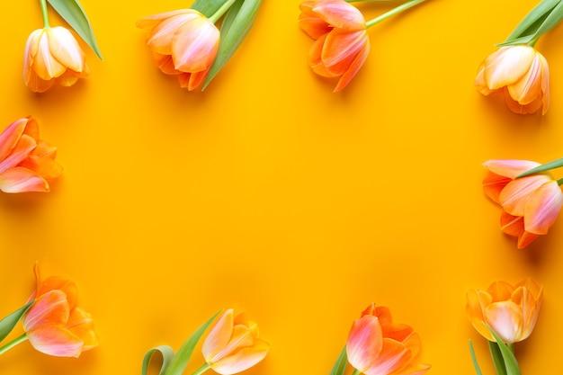 Żółte pastele zabarwiają tulipany na żółtym tle. styl retro vintage. martwa natura, płaska sztuka świecka.
