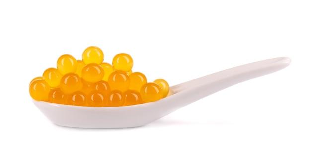 Żółte perły tapioki na herbatę bąbelkową na białym tle. perły tapioki w ceramicznej łyżeczce.