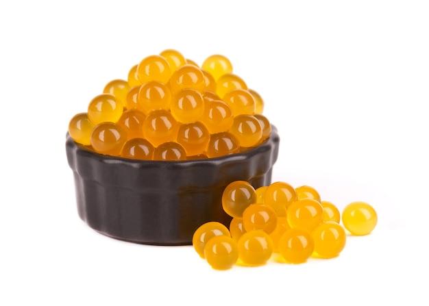 Żółte perły tapioki na herbatę bąbelkową na białym tle. perły tapioki w czarnej ceramicznej misce.