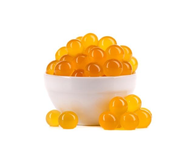 Żółte perły tapioki na herbatę bąbelkową na białym tle. perły tapioki w misce ceramicznej.