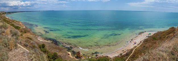 Żółte piaszczyste skały i kamienie o różnych formach na wybrzeżu morza czarnego. błękitne niebo i turkusowa woda.