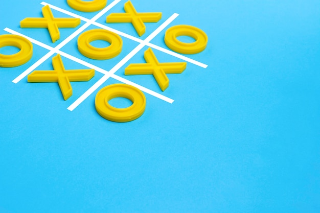 Żółte plastikowe krzyże i palec u nogi oraz pole do gry w kółko i krzyżyk na niebieskiej powierzchni. wyzwanie concept xo win. gra edukacyjna dla dzieci