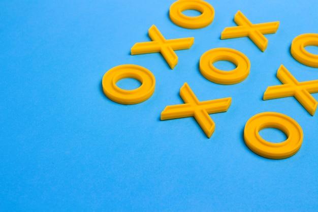 Żółte plastikowe krzyże i zera do gry w kółko i krzyżyk na niebieskiej powierzchni. wyzwanie concept xo win. gra edukacyjna dla dzieci