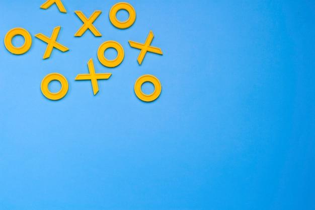 Żółte plastikowe krzyże i zera do gry w kółko i krzyżyk na niebieskim tle. wyzwanie concept xo win. gra rozwojowa dla dzieci. leżał płasko, widok z góry