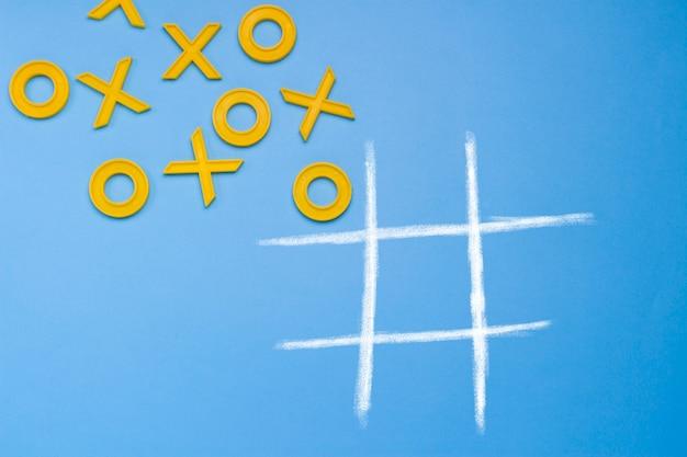 Żółte plastikowe krzyże, palec u nogi i pole do gry w kółko i krzyżyk na niebieskim tle. wyzwanie concept xo win.