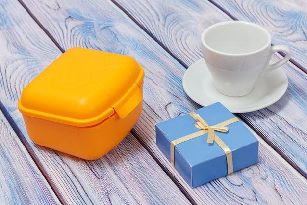 Żółte plastikowe pudełko na lunch, biała porcelanowa filiżanka ze spodkiem i pudełko upominkowe na drewnianej powierzchni