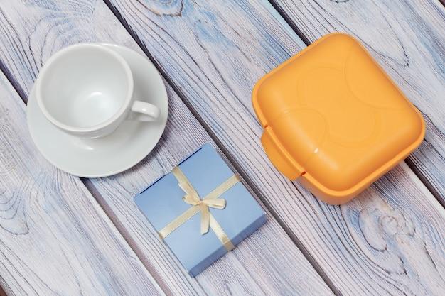 Żółte plastikowe pudełko na lunch, biała porcelanowa filiżanka ze spodkiem i upominkowe pudełko na drewnianym tle.
