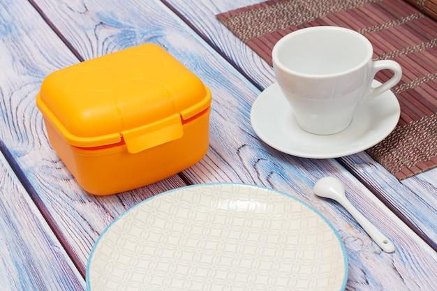 Żółte plastikowe pudełko na lunch, biała porcelanowa filiżanka ze spodkiem na bambusowej serwetce, talerz na drewnianej powierzchni