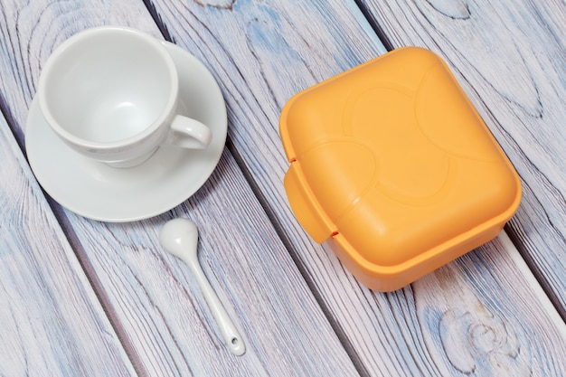 Żółte plastikowe pudełko na lunch i biała porcelanowa filiżanka ze spodkiem na drewnianym tle. widok z góry.