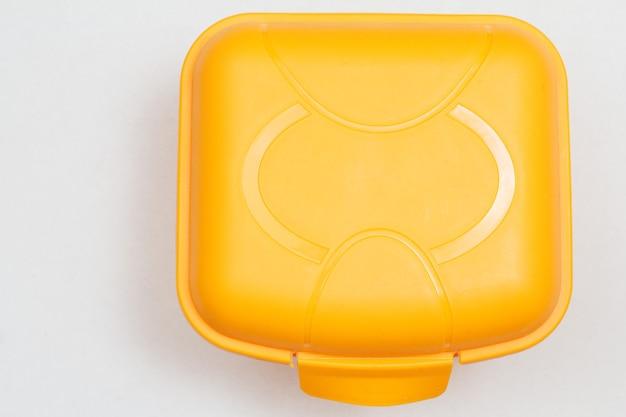 Żółte plastikowe pudełko na lunch na białym tle. widok z góry.