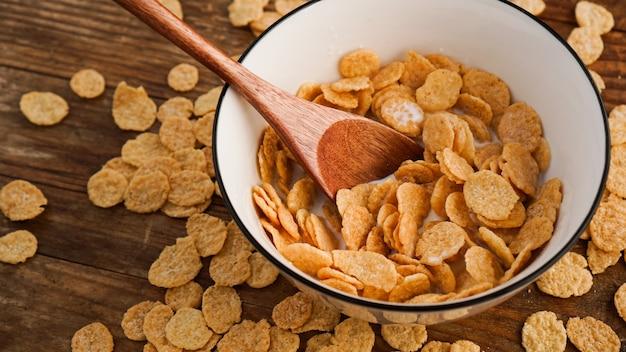 Żółte płatki kukurydziane w białej misce. drewniana łyżka w misce. pojęcie zdrowego odżywiania i pysznego śniadania. tło drewna