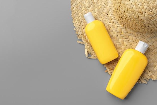 Żółte pojemniki kosmetyczne i słomkowy kapelusz na szarym tle