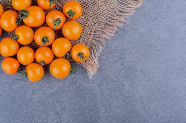 Żółte pomidorki koktajlowe izolowane na niebieskiej powierzchni